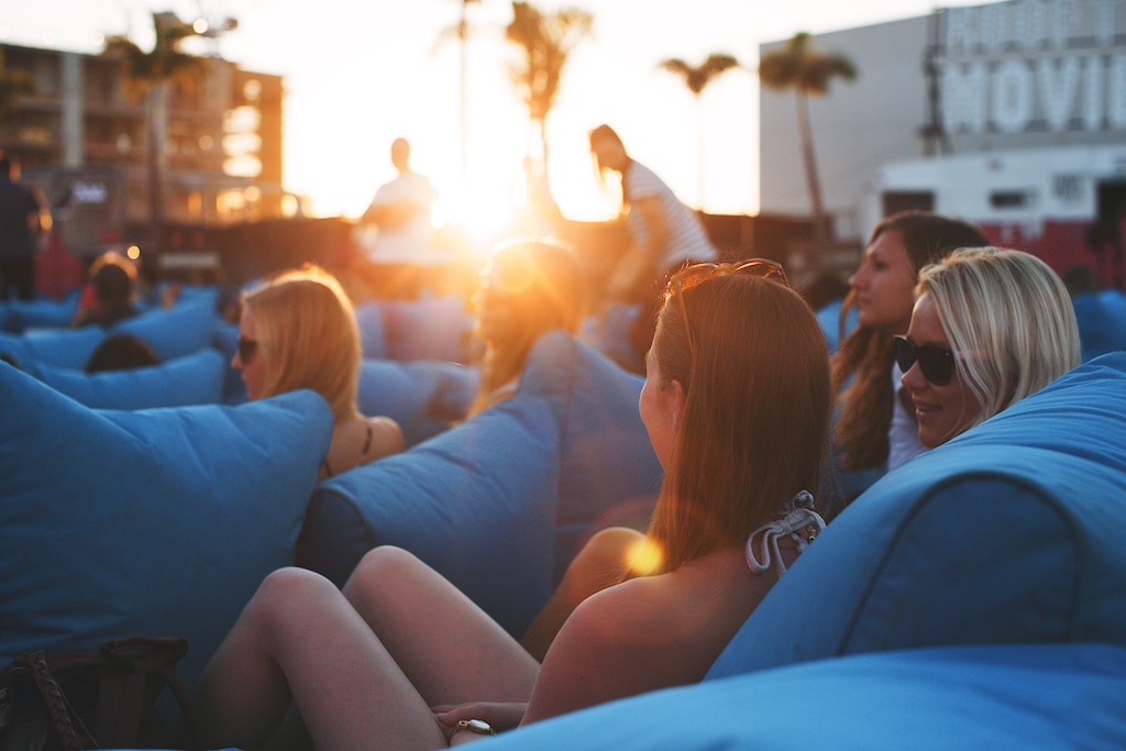 People watching a rooftop movie with sunset in background