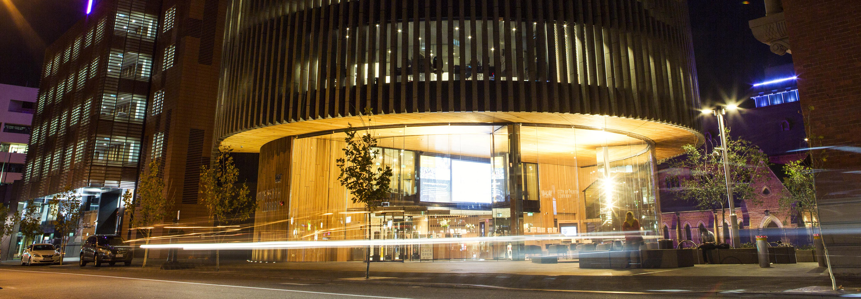 Night shot of Perth City Library with passing cars